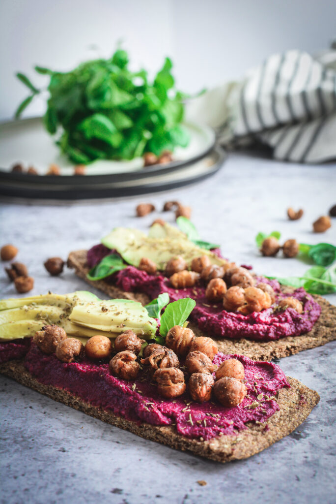 Beet Hummus on two flat breads topped with avocado and crispy chickpeas