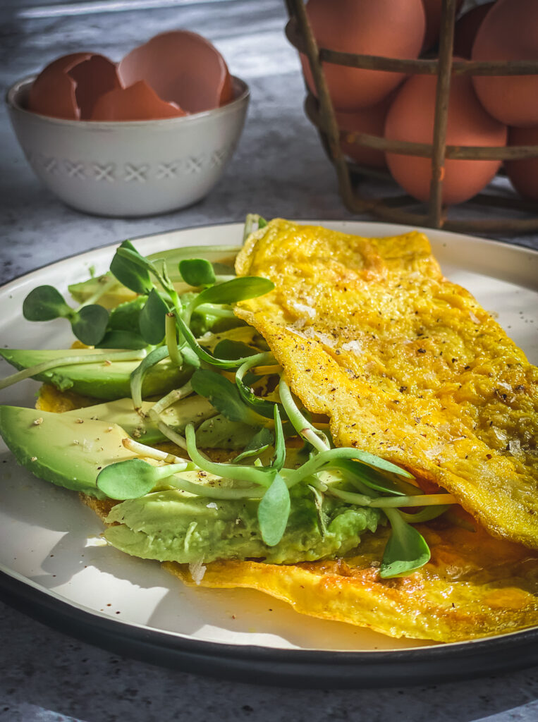 avocado and greens omelette, basket of eggs and bowl of egg shells