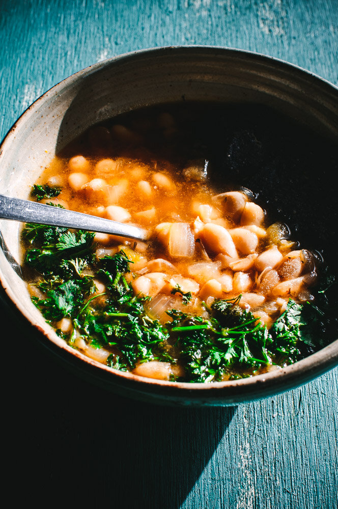 White bean soup in bowl with parsley
