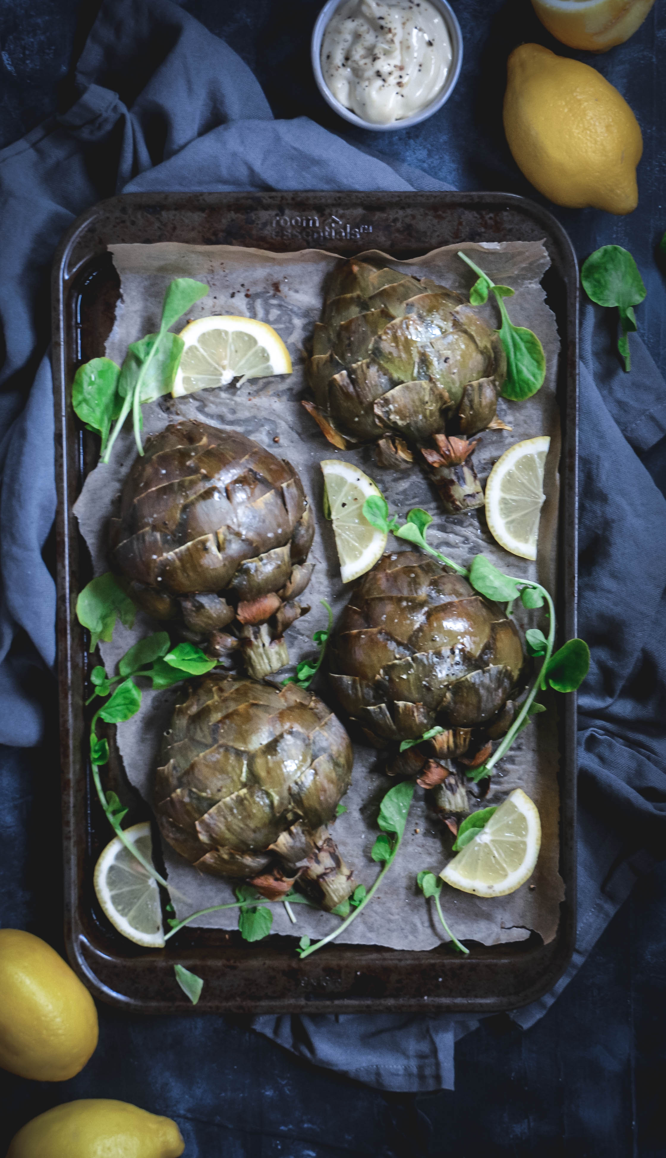 roasted artichokes with lemon slices and lemon aioli and greens