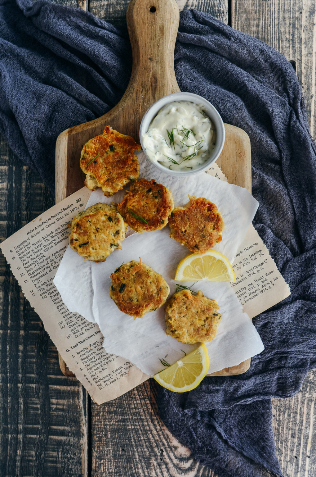 tuna and chickpea bites on cutting board and parchment paper with lemon slices and lemon dill mayo
