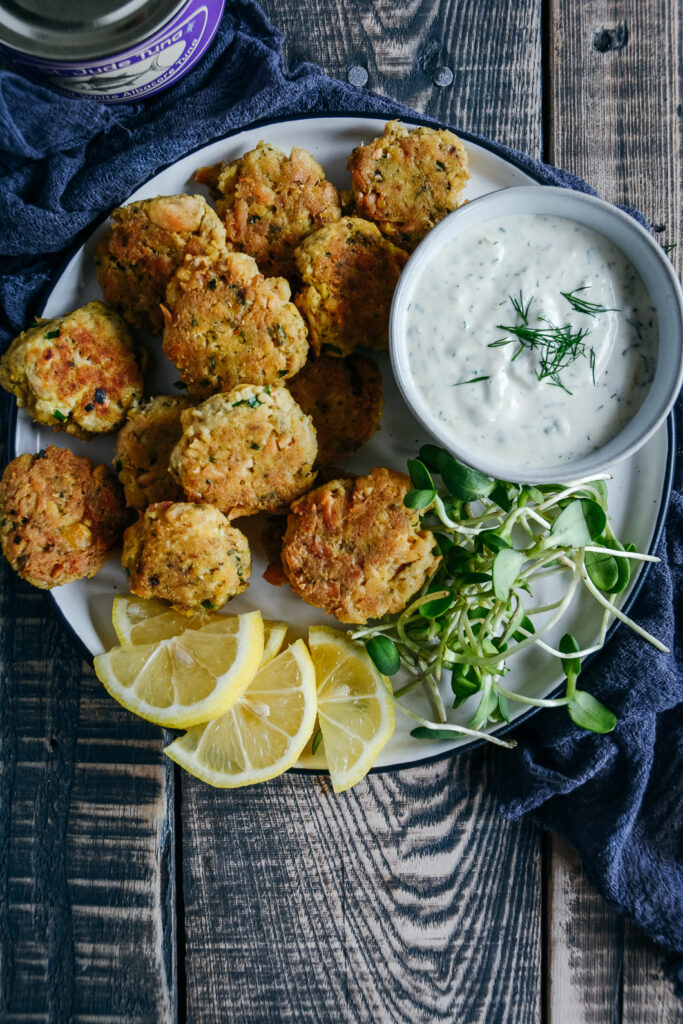 tuna and chickpea bites on plate with greens, lemon slices and lemon dill mayo.