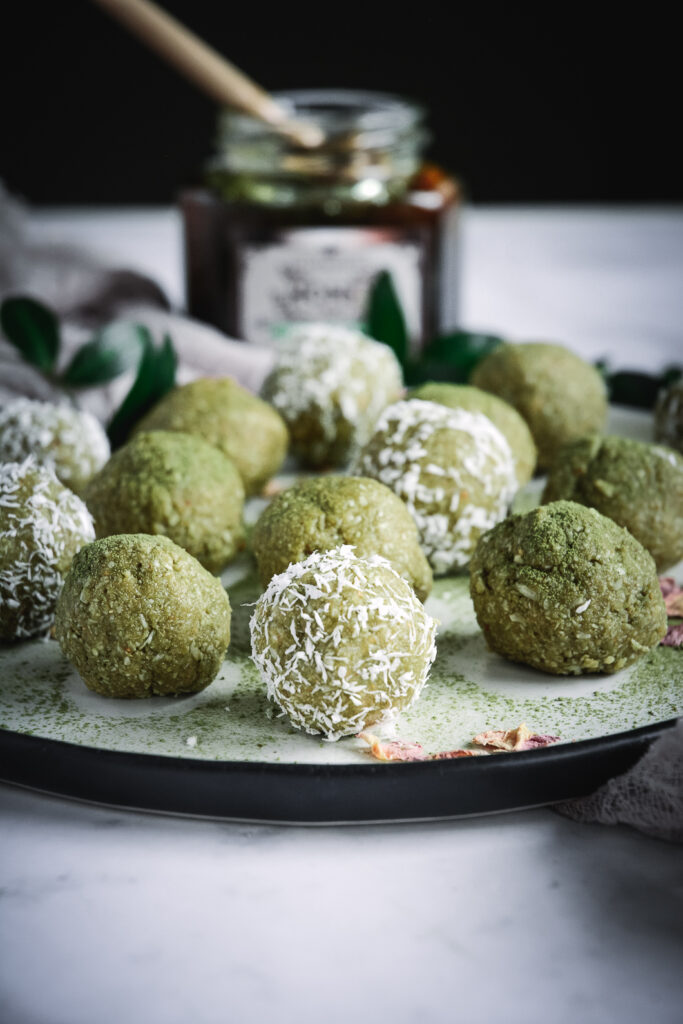 matcha energy balls some covered in shredded coconut on plate